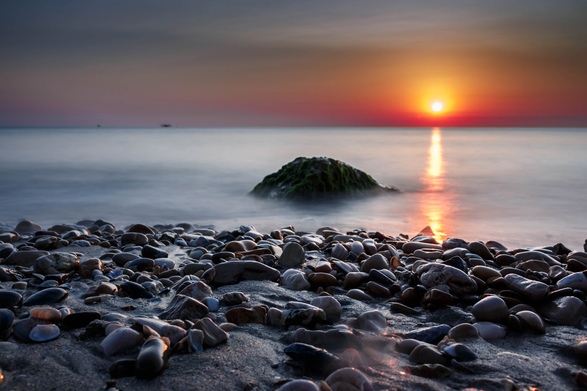 Sunset over a pebbly beach